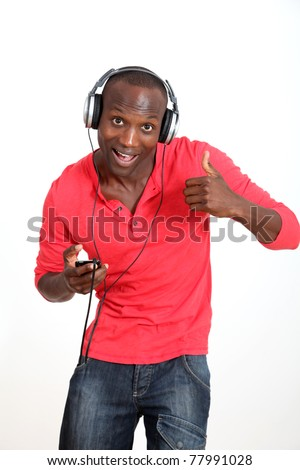 Man with red shirt listening to music with headphones - stock photo