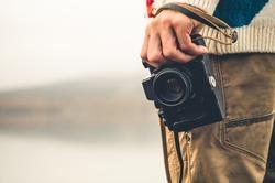 Man with retro photo camera Fashion Travel Lifestyle outdoor foggy nature on background