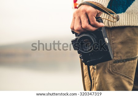 Man with retro photo camera Fashion Travel Lifestyle outdoor foggy nature on background