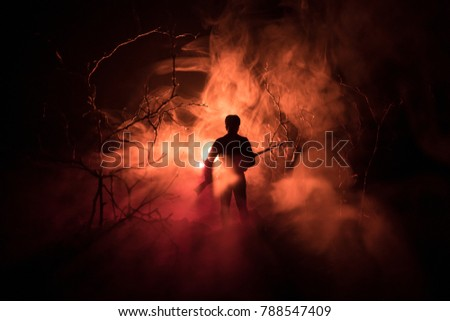 Stock Photo Man with riffle at spooky forest at night with light, or War Concept. Military silhouettes fighting scene on war fog sky background, World War Soldier Silhouette Below Cloudy Skyline At night.