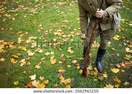 Man with rifle dressed in soviet soldier uniform of World War II hides knife behind boot top.