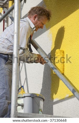 man with roller painting house