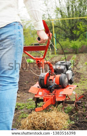 Man with rotating cultivating tiller tractor in the garden