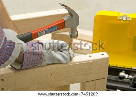 man with safety gloves holding screw and hammer