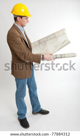 Man with safety helmet looking at architecture blueprints