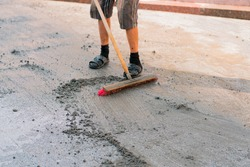 Man with sand and brush closes seams between new installed street tile on the sidewalk. Industry. Worker. Job. Seal the seams between the paving slabs. Water. Wet