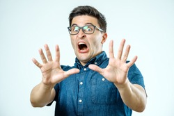 Man with scared expression on his face making frightened gesture with his palms as if trying to defend himself from someone