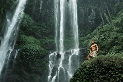 Man With Sexy Fit Healthy Body Relaxing, Standing Near Beautiful Waterfall In Green Jungle Forest. Handsome Fitness Model Enjoying Nature Beauty On Summer Travel Vacation. Water Falling On Background