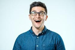 Man with shocked, amazed expression isolated on gray background