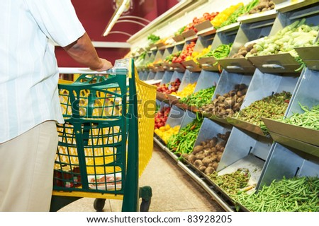 Man with shopping cart during vegetable shopping at the supermarket