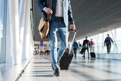 Man with shoulder bag and hand luggage walking in airport terminal