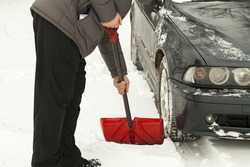 Man with shovel clears snow  around the car