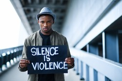 Man with silence is violence sign standing outdoors, black lives matter concept.