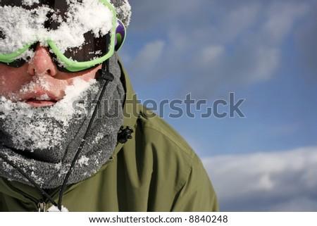 Man with ski goggles on with snow on face from snowball fight.
