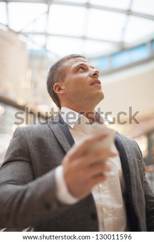 Man with smart phone on hand, blurred background, business building interior