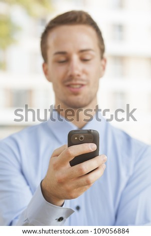Man with smart phone on hand, in blurred background modern business building