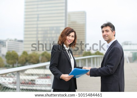 man with smartphone going towards woman with blue folder of documents, old IT business partners meet to discuss work. Middle-aged Americans in strict suits shaking hands smiling. Conce