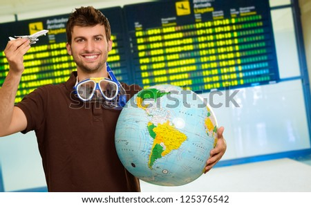 Man With Snorkel Holding Globe And Miniature, Indoors