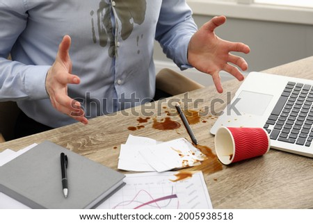 Man with spilled coffee over his workplace and shirt, closeup Foto stock ©
