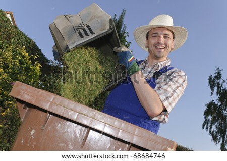 Man with straw hat attacks the organic waste with grass clippings in the garden and laughs at the camera