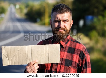 Man with strict face and beard travelling by hitchhiking with road on background. Travelling and hitchhiking concept. Hipster try to stop car with cardboard sign, copy space. #1033720045