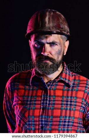 Man with strict face expression isolated on black background. Worker with brutal image wears dirty helmet and plaid shirt. Construction and mining concept. Builder or miner with thick beard #1179394867
