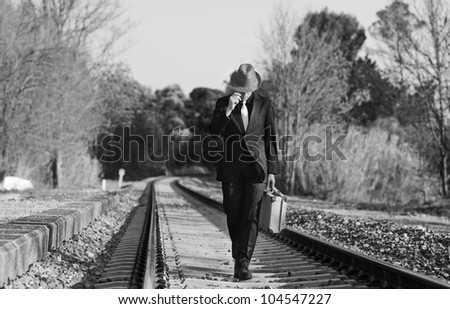 Man with suit , hat and suitcase walking across the railway
