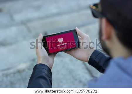 Man with sunglasses and wearing a leather jacket with online dating app on the screen  #595990292