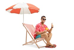 Man with sunglasses drinking cocktail and sitting under umbrella on a deckchair isolated on white background