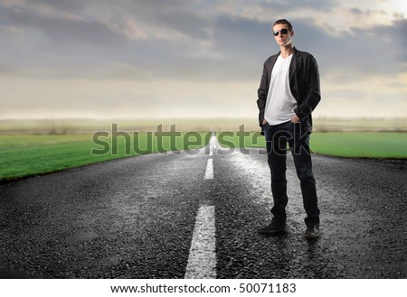 Man with sunglasses standing on a countryside road
