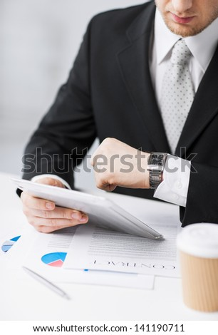 man with tablet pc and cup of coffee looking at watch