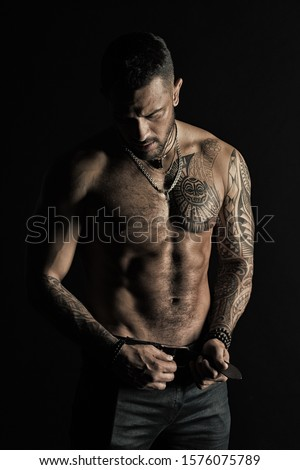 Man with tattoo design on skin. Bearded man shirtless with fit torso. Fashion model buckle leather belt in jeans. Sportsman with six pack and ab. Fitness with sport and bodycare, vintage filter.