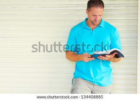 Man with Tattoo Reading The Bible