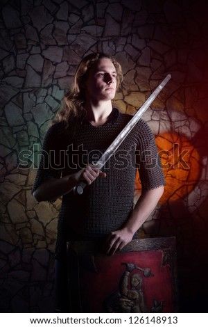 Man with the sword against the brick wall