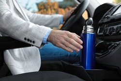 Man with thermos driving car, closeup view