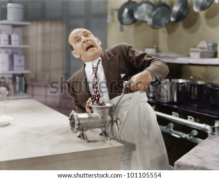 Man with tie stuck in meat grinder