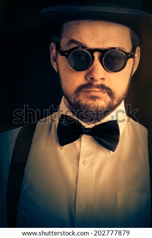 Man with Top Hat and Steampunk Glasses Retro Portrait - Gentleman portrait, young bearded man wearing steampunk glasses, bowtie and top hat