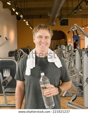 Man with towel and water bottle in health club
