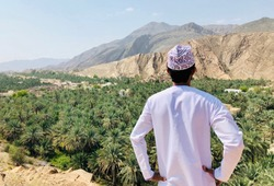 Man with traditional Arabic clothes observing palm trees in the desert