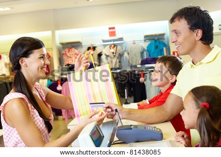 Man with two children paying for purchases