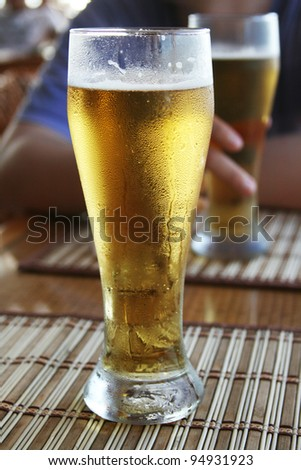 Man with two glasses of beer in open air pub