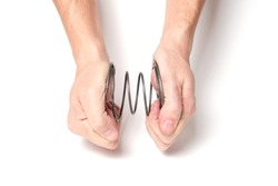 Man with two hands squeezes a spring on a white background