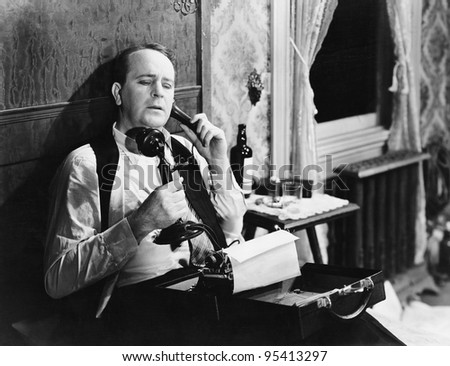 Man with typewriter talking on phone - stock photo