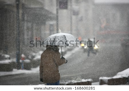 Man with umbrella during snow storm in the street