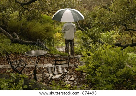 Man with umbrella waits out the rain among trees