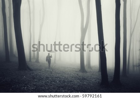 man with umbrella walking in a dark forest with fog and black trees