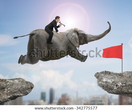 Man with using speaker riding elephant flying toward red flag on cliff, with sunny sky cityscape background.