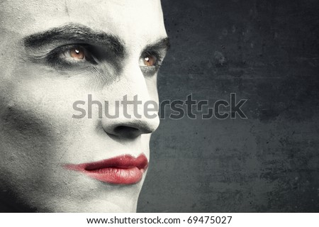 Man with vampire makeup on a dark grungy background. Natural makeup and background. Text can be added onto the empty space