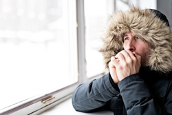 Man With Warm Clothing Feeling The Cold Inside House close to a window