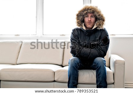 Man With Warm Clothing Feeling The Cold Inside House on the sofa #789353521